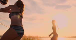 Sexy girls volleyball players pass the ball near the net and hit the ball at sunset in slow motion.  stock footage