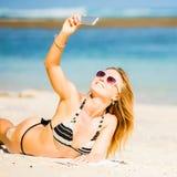 Sexy glückliche blonde junge Frau beim Sonnenbrillenehmen Stockbild