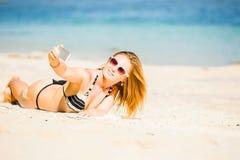 Sexy glückliche blonde junge Frau beim Sonnenbrillenehmen Lizenzfreie Stockbilder
