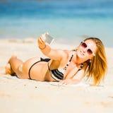 Sexy glückliche blonde junge Frau beim Sonnenbrillenehmen Stockfotografie
