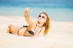 Sexy glückliche blonde junge Frau beim Sonnenbrillenehmen Lizenzfreie Stockfotografie