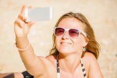 Sexy glückliche blonde junge Frau beim Sonnenbrillenehmen Stockfotos