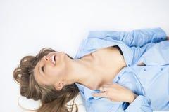 Sexy glückliche kaukasische blonde Frau im blauen Hemd, das auf Boden liegt Lizenzfreie Stockfotografie