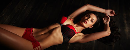 Sexy glamorous brunette woman with beautiful long hair in black and red lingerie Royalty Free Stock Images