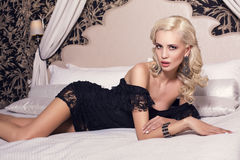 Sexy glamour blond woman in elegant black dress Stock Photos