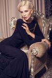 Sexy glamour blond woman in elegant black dress. Sitting on the armchair in bedroom Royalty Free Stock Images