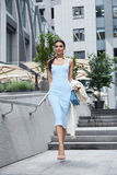 Sexy glamour woman in blue fashion style dress with handbag. Accessory and coat golden jewelry businesswoman walk buildings and trees street brunette wear shoes Stock Image