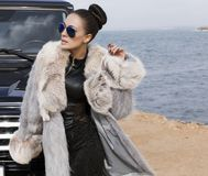 Sexy glamour woman with fur coat posing beside a Stock Image
