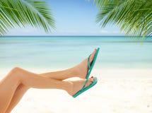 Sexy glatte Frauenbeine mit Strand auf Hintergrund Stockfotos