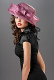 Sexy goddess. A portrait of a sexy brunette wearing a black retro dress and a rosy designer hat Stock Photography