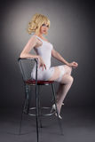 Sexy gold blond woman sit on bar chair Royalty Free Stock Images