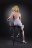 Sexy gold blond woman sit on chair Stock Image