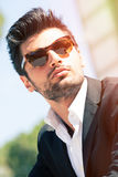 Sexy gorgeous stylish man. Sunglasses. A beautiful and charming man with sunglasses outdoors. Stubble and blacks hair. Intense light. White shirt and stylish Stock Photography