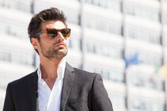 Sexy gorgeous stylish man. Sunglasses. City style. A beautiful and charming man with sunglasses outdoors. Stubble and blacks hair. Intense light. White shirt and Stock Image