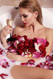 gorgeous woman with blond hair relaxing in bathroom with rose petals, drinking champagne Stock Image