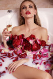 gorgeous woman with blond hair relaxing in bathroom with rose petals, drinking champagne Stock Photo