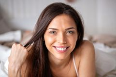 Gorgeous young woman smiling on her bed showing off with her beauty royalty free stock image