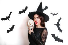 Happy gothic young woman in witch halloween costume with hat standing and having fun over white background. Gothic young woman in witch halloween costume with stock photos