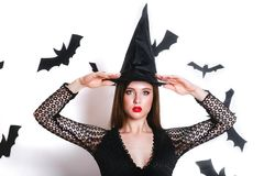 Happy gothic young woman in witch halloween costume with hat standing and smiling over white background. Gothic young woman in witch halloween costume with hat royalty free stock photos
