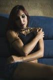Sexy gotische Frau 20s, die im Sofa sich entspannt Lizenzfreie Stockfotos