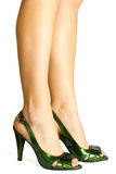Green leather high heels stilettos shoes. And woman's legs isolated on white background royalty free stock image