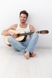 Sexy guitarist sitting on floor smiling Royalty Free Stock Photo