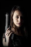 Sexy Gun Woman. Shot of a beautiful girl holding gun, isolated on black bckground Stock Photo