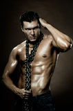 Sexy guy. The very muscular handsome sexy guy on dark  brown background, with neckcloth of  chain on neck Royalty Free Stock Photography