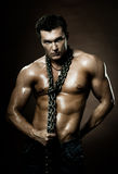 Sexy guy. The very muscular handsome sexy guy on dark  brown background, with neckcloth of  chain on neck Royalty Free Stock Photo