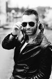 Sexy guy with attitude wearing leather jacket and sunglasses out Stock Image