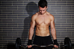 Sexy guy with a beautiful muscular figure is engaged in an expensive sports club Stock Photography