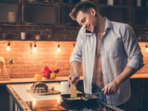 Sexy guy cooking. Handsome guy is talking on the mobile phone and smiling while cooking in the kitchen Royalty Free Stock Photos