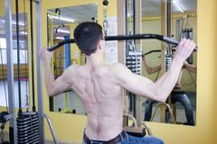 Sexy guy with a naked torso. in the gym. Crossbeam to itself to swing muscles Stock Photo