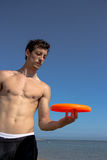 Guy play with frisbee on the beach. A guy let the frisbee roll on his finger stock photo