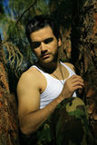 Sexy guy in tree. Dramatic stylized portrait of sexy young man in tree Royalty Free Stock Photo