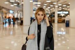 Sexy hübsche stilvolle junge blonde Frau mit grauen Augen in einem luxuriösen grauen Mantel mit einem Weinleseschal mit einer mod stockfotografie