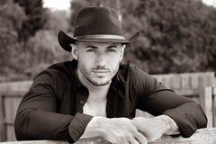 Sexy, hübscher, hunky Cowboy mit offenem Hemd des Hutes und Pecs betrachtet Kamera lizenzfreie stockbilder