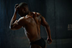 Sexy handsome african american male body builder posing on a black studio background. Beauty and perfection of human Royalty Free Stock Images