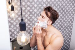 Sexy handsome man shaving his face before going to the office. Before office. Sexy handsome dark-haired man shaving his face before going to the office stock photography