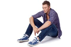 Sexy handsome man sitting on the floor Stock Images