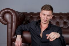 Sexy handsome man wearing black shirt sitting on floor near the leather sofa. Comfort and relaxation royalty free stock photography
