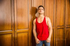 Sexy handsome young man standing against wardrobe. Sexy handsome young man standing, wearing red tank-top in his bedroom against wooden wardrobe door Royalty Free Stock Photos