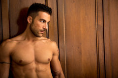 Sexy handsome young man standing shirtless against Royalty Free Stock Images