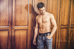 handsome young man standing shirtless against wardrobe stock photo