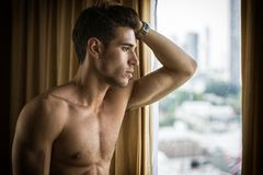 Sexy young man standing shirtless by curtains royalty free stock image