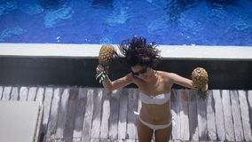 Sexy happy brunette in white bikini jumping near swimming pool and dancing with two pineapples on wooden deck of private. Sexy happy brunette in black sunglasses stock footage