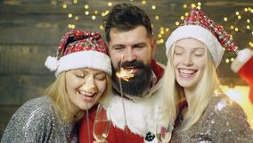 Sexy happy group of friends at glamorous party lighting sparklers having fun smiling celebrating new year`s eve. They. Are happy. Waiting for Santa Claus. Man stock footage