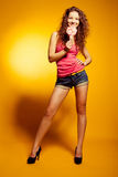 Sexy happy woman dancing excited on yellow Royalty Free Stock Photos