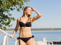 Sexy, healthy woman in a bikini on a natural river background. Young beauty concept. Copy space. Stock Photo