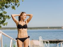 Sexy, healthy woman in a bikini on a natural river background. Young beauty concept. Copy space. Stock Photography
